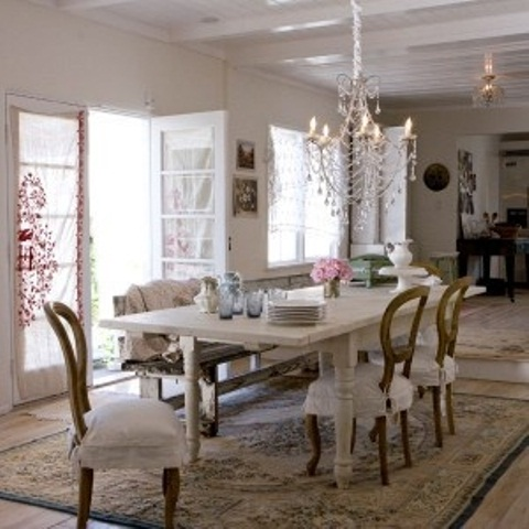 a simple shabby chic dining space done in neutrals, with a vintage crystal chandelier, vintage furniture and a cool rug