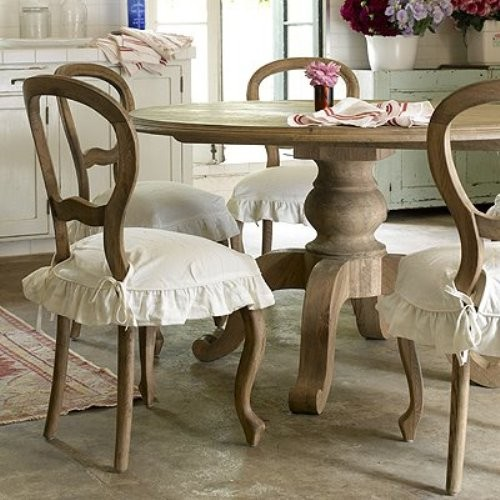 a rustic meets shabby chic dining room with vintage wooden furniture, white ruffle covers and chic white furniture for storage
