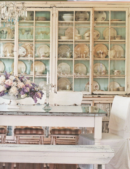 a gorgeous shabby chic dining room with a large shelving unit that takes a whole wall, shabby chic vintage furniture and a crystal chandelier