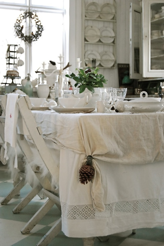 a cozy neutral shabby chic dining room with white walls and furniture, with layered tablecloths and simple white porcelain