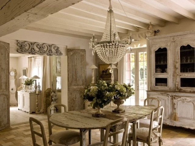 a shabby chic dining room with French charm, with vintage furniture, a large crystal chandelier, potted greenery and blooms