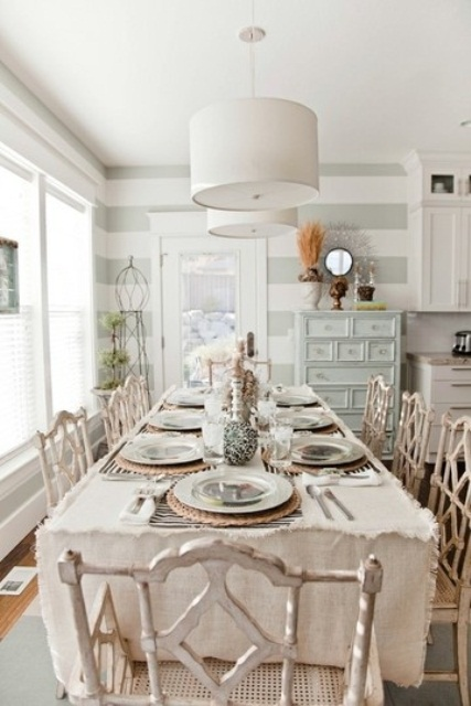 a shabby chic meets coastal dining room with shabby furniture, striped walls, pastel items and wicker touches