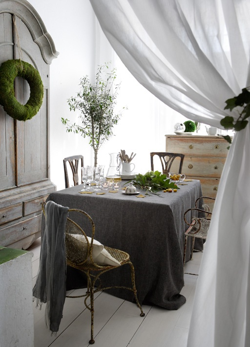 a shabby chic meets Scandinavian dining room with neutral and dark linens, shabby chic furniture and some greenery and moss to refresh the space