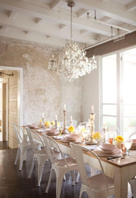 a shabby chic meets rustic dining room with a rustic table and metal chairs, a chic crystal chandelier and shabby chic walls