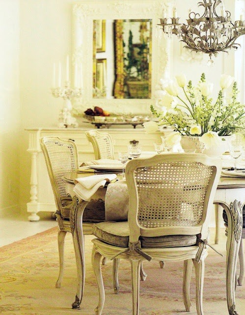 an elegant vintage or shabby chic dining space with a chic and stylish dining set, a vintage chandelier and some vintage furniture