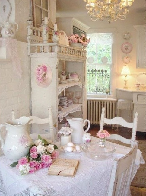 a shabby chic dining room in white with pink touches, with cool shabby chic furniture, a ruffle tablecloth, vintage porcelain and blooms plus a vintage chandelier