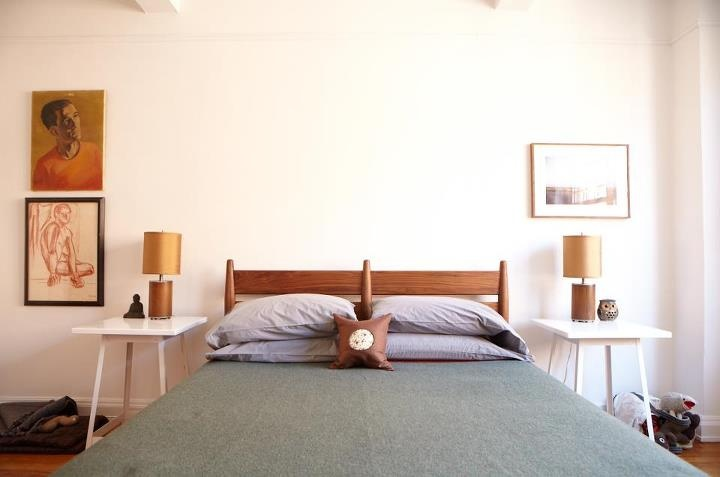 a rich stained wooden bed with striped headboard and simple white stools as nightstands is a bold and cool idea