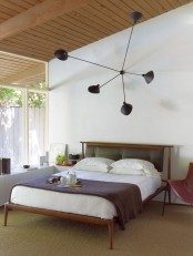 a quirky rich-stained wooden bead with a black leather tufted headboard is amazing for a mid-century modern space