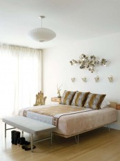 a neutral wooden bed with hairpin legs and floating wooden nigthstands for a stylish mid-century modern space
