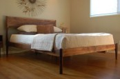 a simple and elegant stained wooden bed with a headboard and tall legs is cool and chic