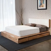 a light-stained platform mid-century modern bed with drawers and a minimal white headboard attached to the wall