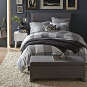 a light grey upholstered bed and a matching chest for storage will make your mid-century modern bedroom welcoming