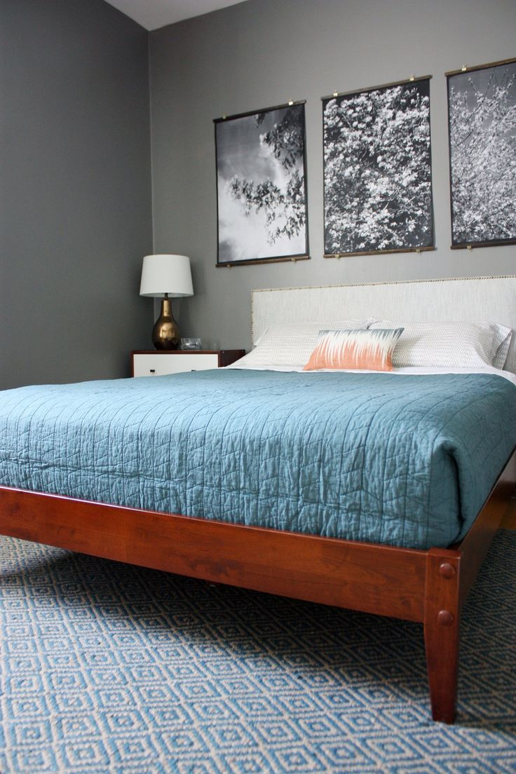 a redwood bed with a white upholstered headboard and white and rich stained wooden nightstands for a chic mid century modern bedroom