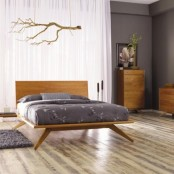 a stylish light-stained mid-century modern bed on tall legs and with a simple headboard for making the space cozier