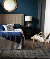 a neutral bed with an oversized upholstered tufted headboard and grey box nightstands for a bold and cool mid-century modern look