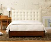 a rich stained wooden bed with a white leather tufted headboard looks chic and refined and will make a statement in a mid-century modern room