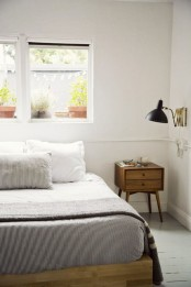 a simple and laconic light-stained wooden bed for a stylish neutral mid-century modern bedroom