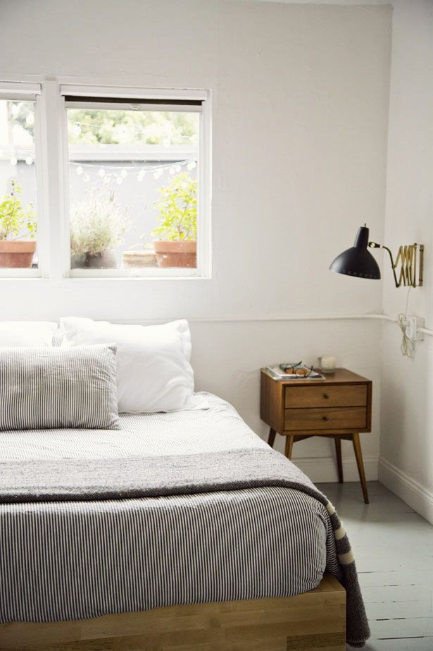 a simple and laconic light stained wooden bed for a stylish neutral mid century modern bedroom