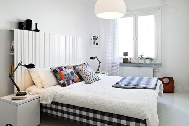 a plaid black and white bed and a light wooden headboard with storage space makes the bedroom welcoming and cool