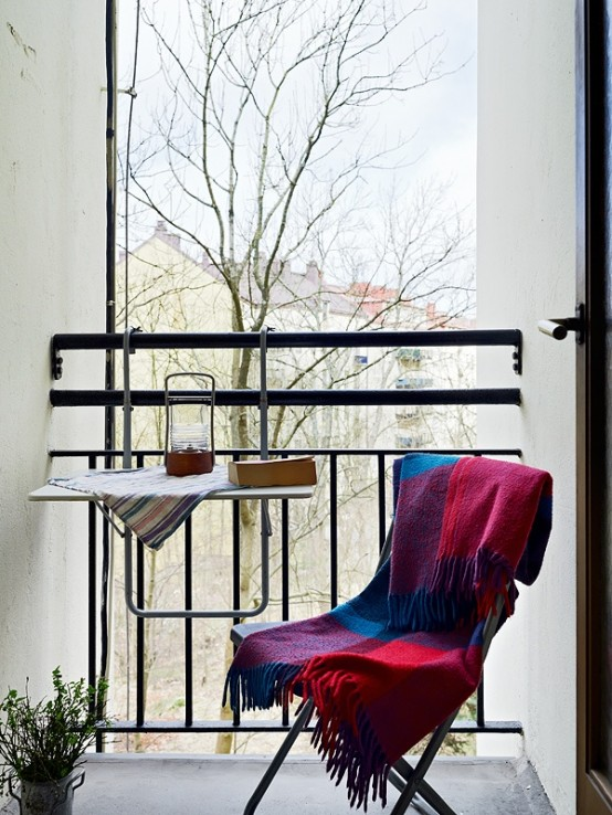 Cozy plaid blanket is a perfect addition for a balcony's chair cuz it isn't always summer out there.