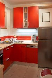 a bright kitchen with red cabinetry and a bold tile backsplash, neutral tiles and a stainless steel fridge