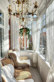 a vintage-inspired sunroom with a large crystal chandelier, lace curtains and wicker chairs