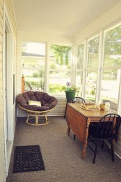 a sunroom dining/playing space with a foldable table, some chairs and an upholstered round chair