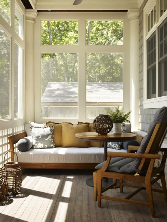 a tiny mid century modern sunroom with some comfortable furniture,wicker lamps and potted greenery