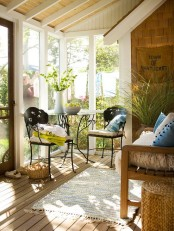 a chic eclectic sunroom space with forged chairs and a table and a wooden benches with textiles and accessories