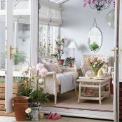 a traditional sunroom with white wicker furniture, printed and colorful textiles, lamps, mirrors and potted flowers