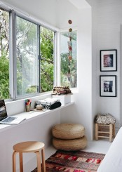 a contemporary sunroom space as a home office or an art space with a windowsill desk, some stools and ottomans