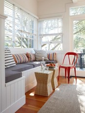a small sunroom living room with a large built-in bench with storage and a duo of wicker stools