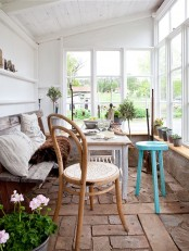 a vintage Scandianvian sunroom with a comfy bench and a long windowsill with potted blooms and greenery and a dining table of wood