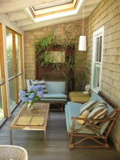 a mid-century modern sunroom done in sandy shades, with rattan chairs, pendant lamps and potted greenery
