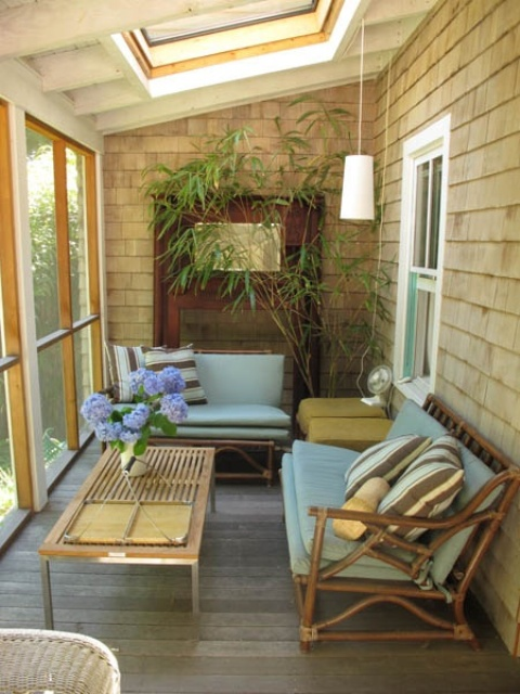 a mid century modern sunroom done in sandy shades, with rattan chairs, pendant lamps and potted greenery