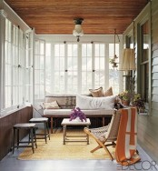 a retro-inspired sunroom with wooden and wicker furniture, lamps and lights and touches of color