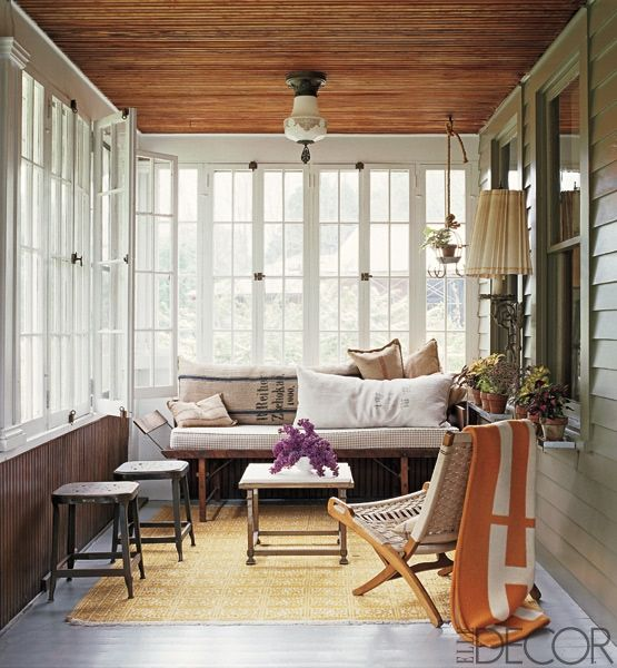 a retro inspired sunroom with wooden and wicker furniture, lamps and lights and touches of color