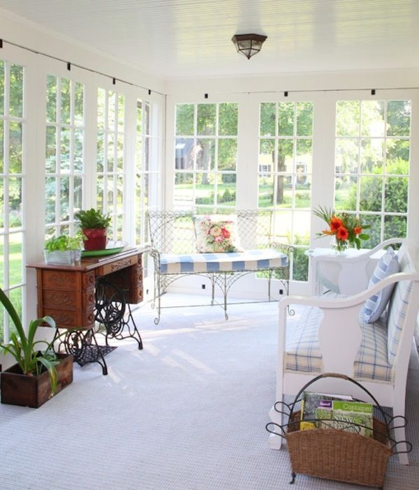 an exquisite sunroom with garden forged furniture, a large white bench, a vintage desk and a basket