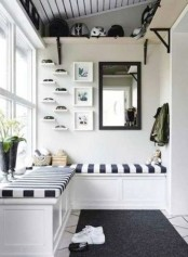 a monochromatic space with a striped built-in bench, a rug and some shelves for storage