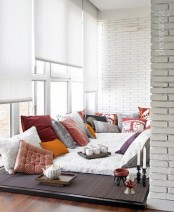 a chic contemporary sunroom nook with a sitting place right on the floor and lots of pillows for a boho feel