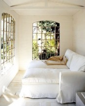 a sophisticated small sunroom with comfortable lounge chairs and French windows that brign elegance