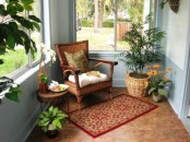 a welcoming sunroom nook with potted greenery and blooms and wicker furniture and accessories plus a rug