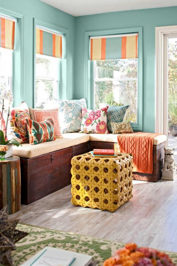 a small and colorful sunroom with turquoise walls, colorful and printed details and a wicker ottoman