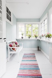 a small pastel sunroom in a light aqua shade, colorful textiles and a bench plus potted blooms
