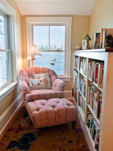 a sunroom turned into a reading nook with a large bookshelf and a pink lounge chair plus a lamp