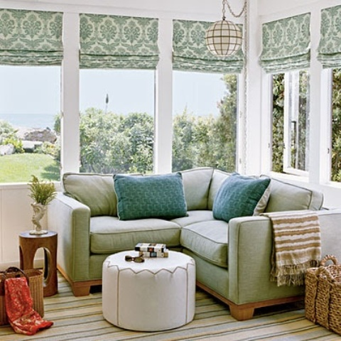 a refreshing sunroom nook with green shades and furniture, comfy ottomans and colorful touches