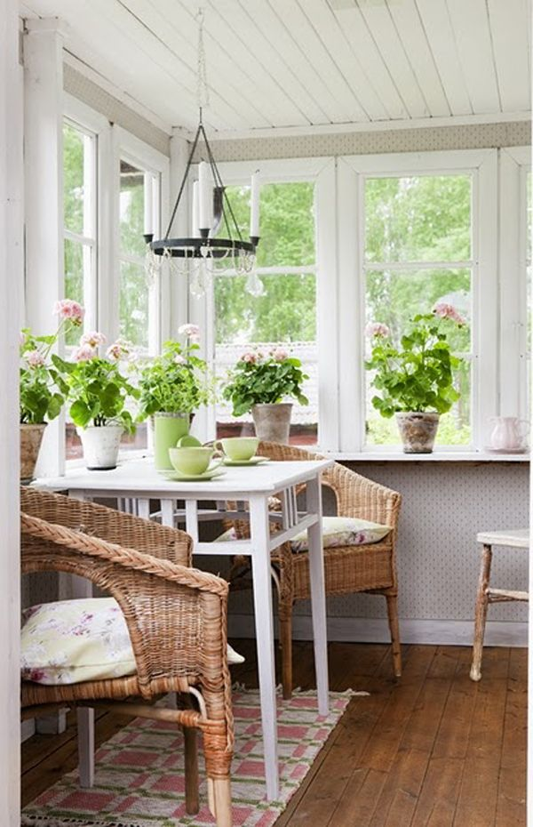a sunroom with a meal space of a white table and wicker chairs and lots of potted flowers
