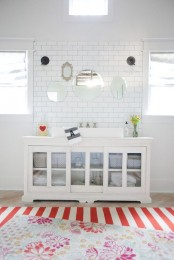 a white vintage sideboard as a bathroom vanity, with glass doors and baskets for storage is a lovely idea for a modern space, too