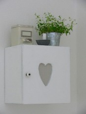 a small whitewashed cabient with a cutout heart is a pretty solution for a Scandinavian or shabby chic space and it looks amazingly cute