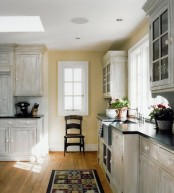a vintage planked whitewashed kitchen with black countertops and a matching whitewashed backsplash is a gorgeous idea with a contrast